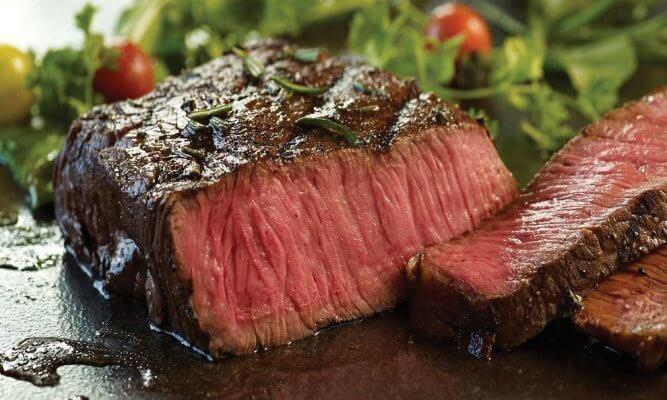 A rare steak cut in half on plate