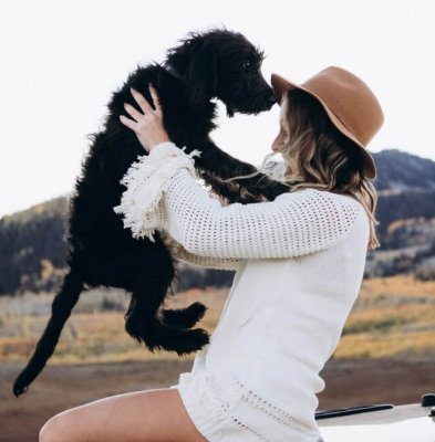 Woman in hat holds scruffy dog against mountain backdrop